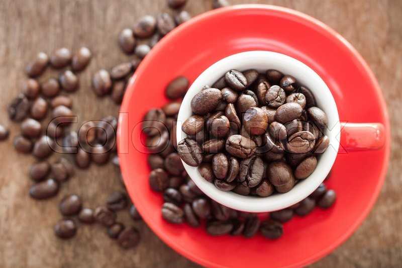 Stock image of 'Red coffee cup with coffee beans on wooden table, stock photo'