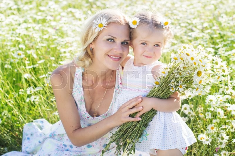 Stock image of 'Mother with cute little child girl are wearing white clothes in the chamomile field in spring'