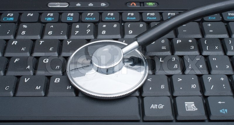 Medical stethoscope laying on a computer keyboard, stock photo