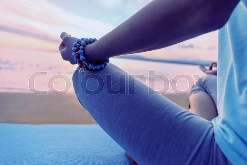 Stock image of 'Woman meditating in pose of lotus on beach in summer in the morning, close-up'