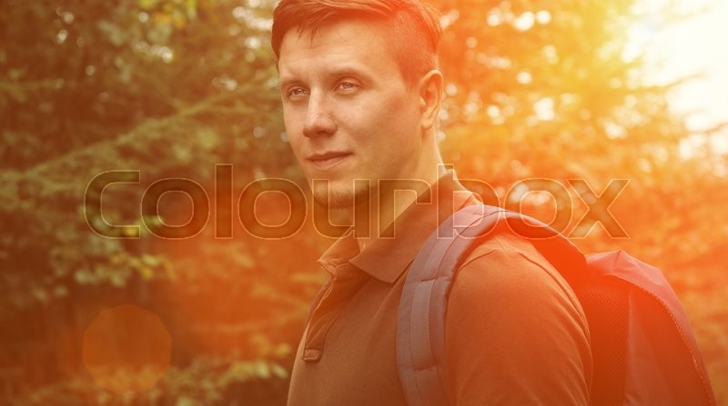 Stock image of 'Smiling hiker young man walking in summer forest at sunny day. Image with sunlight effect'