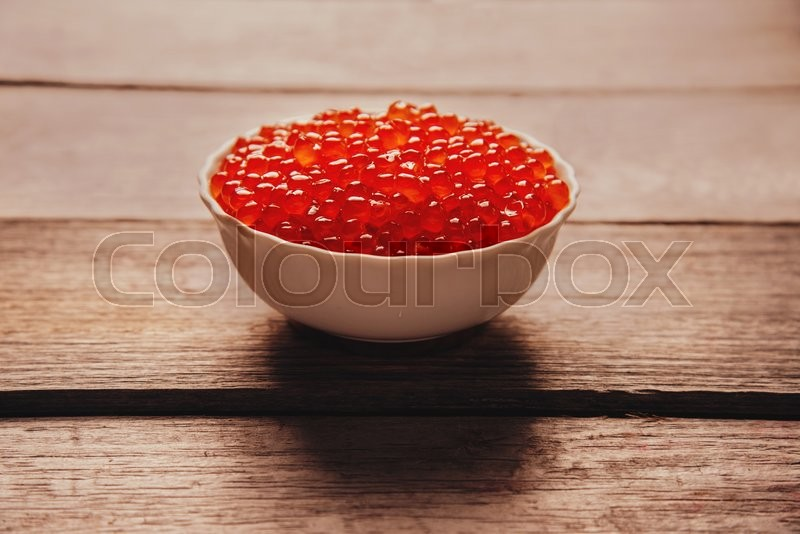 Stock image of 'Red salmon caviar in a white bowl on wooden background'