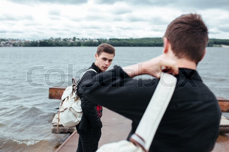 Stock image of 'two young guys standing on a pier and a little further'