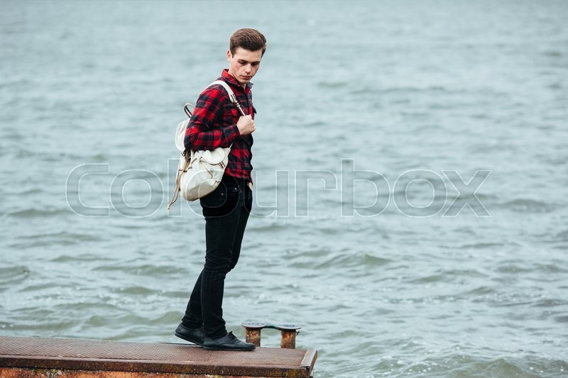 Stock image of 'the young man posing on a pier on the background of water'