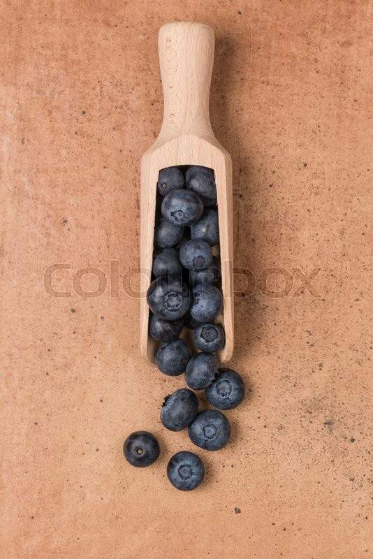 Stock image of 'Blueberries on a wooden spoon against stone textured background.'