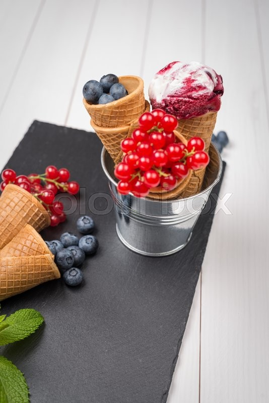 Stock image of 'Red fruits ice cream cone on black slate board.'