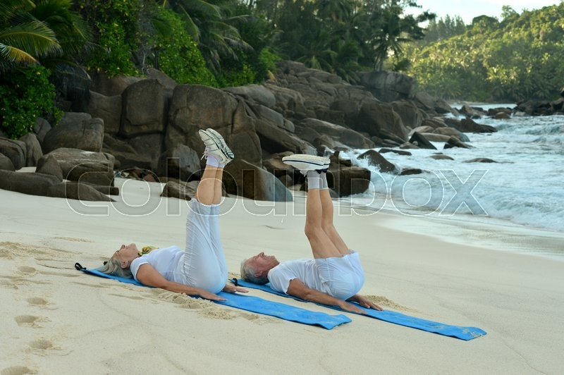 Stock image of 'Happy Senior couple exercising in summer on  seashore'