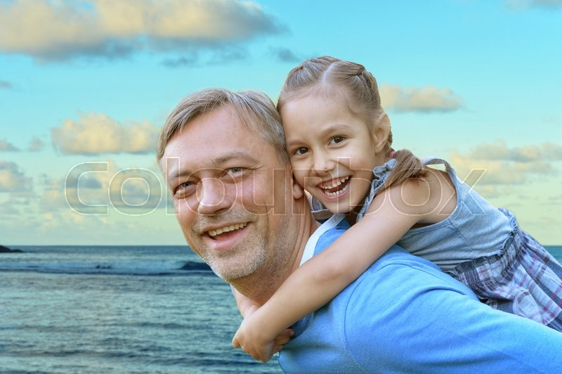Stock image of 'Happy father with daughter against the sea'