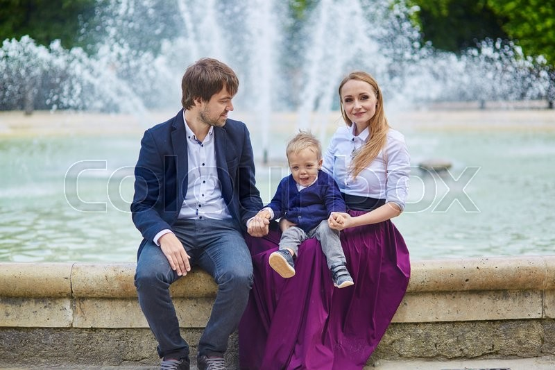 Stock image of 'Happy family of three in the beautiful garden of Palais Royal in Paris on a summer day'