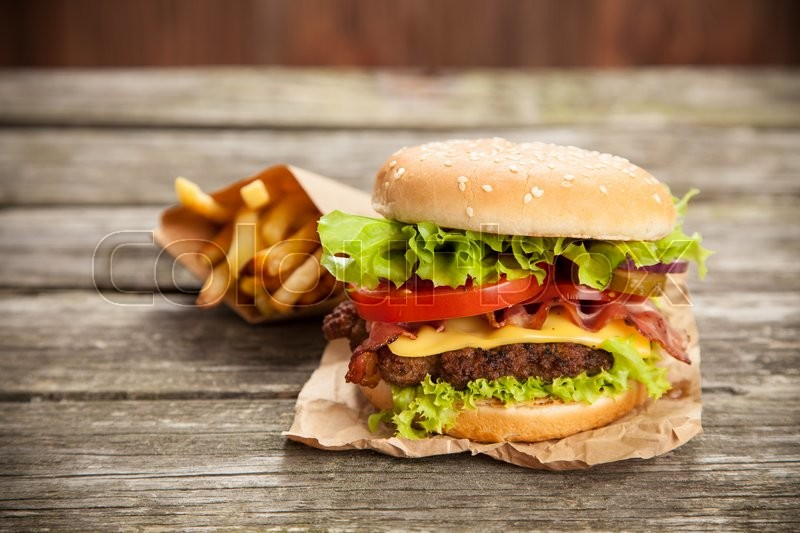 Stock image of 'Delicious hamburger and french fries on wooden background'