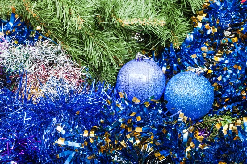 Stock image of 'Christmas still life - pair of blue and violet Christmas balls, tinsel on Xmas tree background'