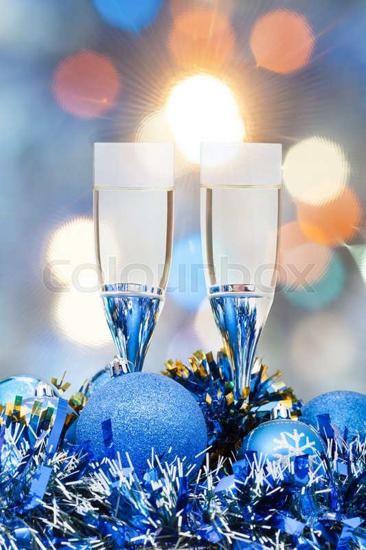 Stock image of 'Christmas still life - two glasses of champagne at blue Xmas decorations with pink and blue blurred Christmas lights background'