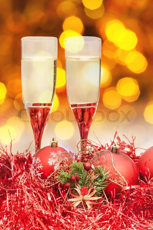 Stock image of 'Christmas still life - two glasses of champagne at red Xmas decorations with yellow and violet blurred Christmas lights background'