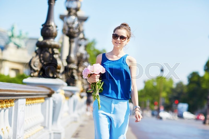 Stock image of 'Beautiful young Parisian woman in blue tube top with bunch of pink peonies on the bank of the Seine'