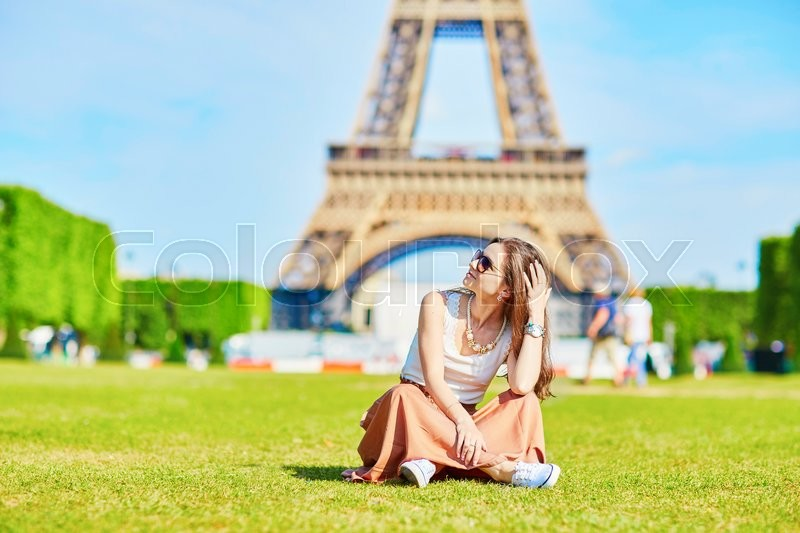 Stock image of 'Beautiful young tourist or student girl in Paris sitting on the grass near the Eiffel tower on a summer day'