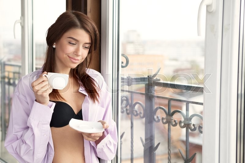 Stock image of 'Young sexy woman wearing man's shirt and enjoying her morning coffee'