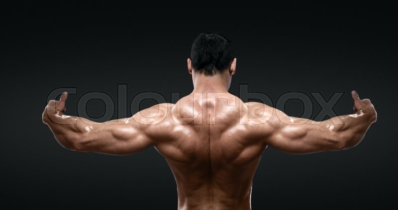 Stock image of 'Rear view of healthy muscular young man with his arms stretched out isolated on black background'