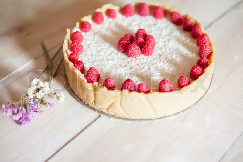Stock image of 'Raspberry cheesecake on a white wood background'