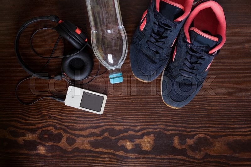 Stock image of 'Sport equipment. Sneakers, water, earphones and mp3 player on wooden background'