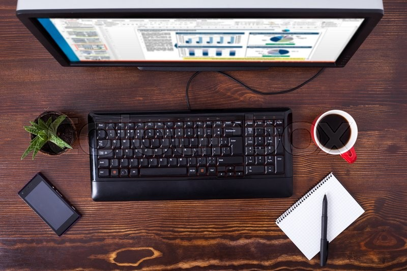 Stock image of 'Office business workplace with desktop computer, cup of black coffee and phone on wooden table'