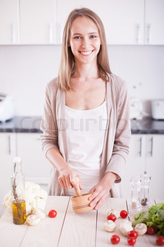 Stock image of 'Young Woman Cooking in the kitchen. Dieting vegetarian concept. Healthy Lifestyle. Cooking At Home. Prepare Food'