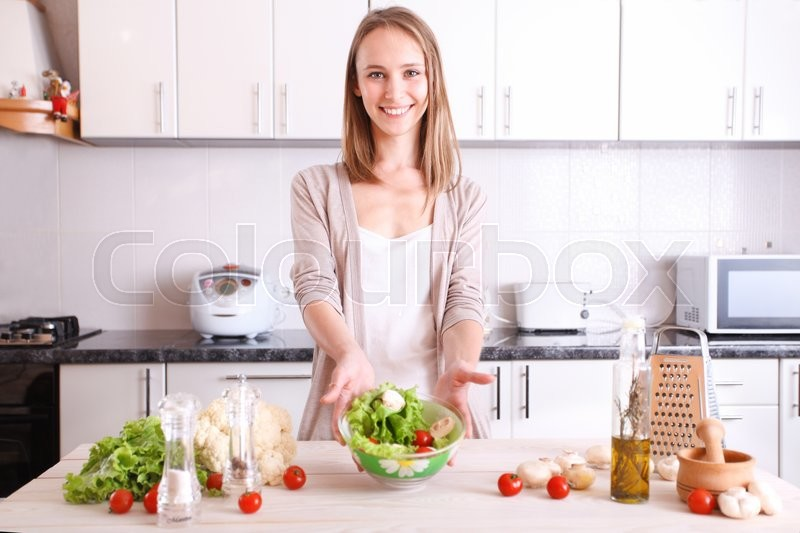 Stock image of 'smiling woman making healthy food in kitchen'
