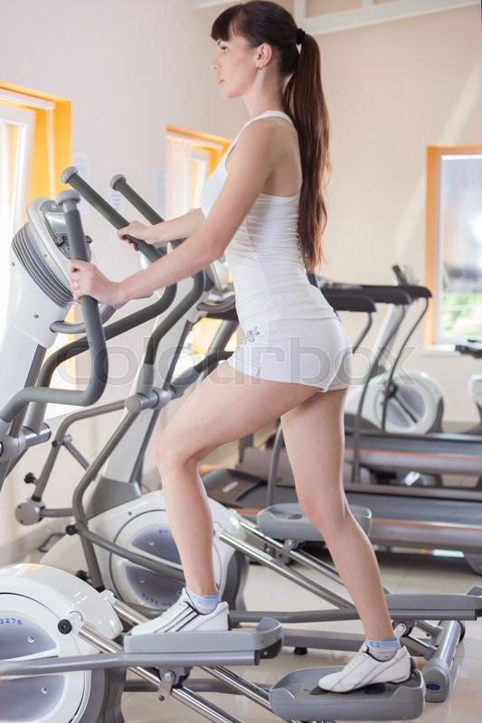 Stock image of 'woman with elliptical cross trainer in sport fitness gym club'