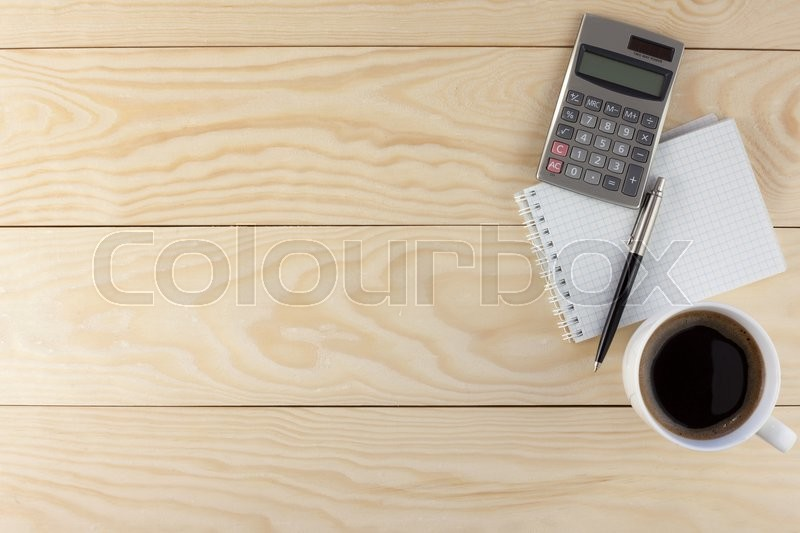 Stock image of 'Calculator,  spiral note pad, coffee and pen on wood background'