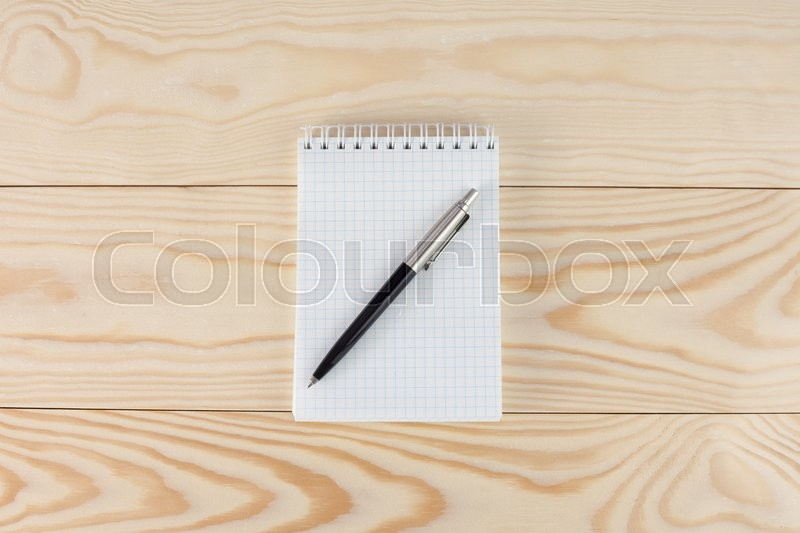 Stock image of 'spiral notepad with pen  onwooden table'