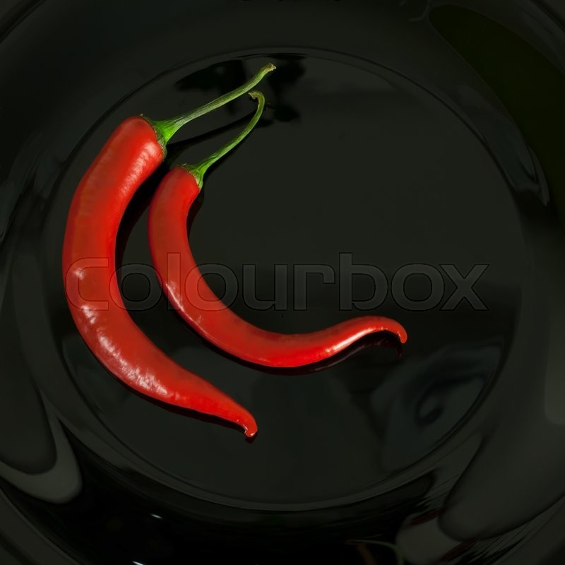 Stock image of 'red chili pepper on black background'