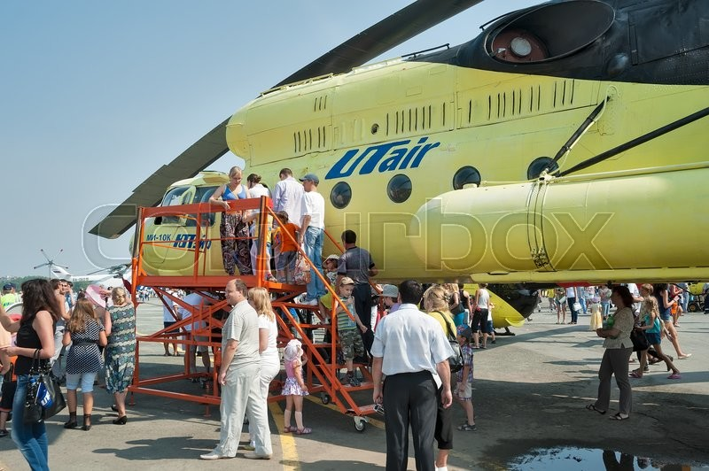 "Editorial image of 'Tyumen, Russia - August 11, 2012: Air show ""On a visit at UTair"" in heliport Plehanovo. Passengers make landing in Mi-10K helicopter'"