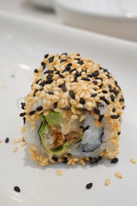 Stock image of 'Maki Sushi - Roll with avocado,  Sesame outside. '