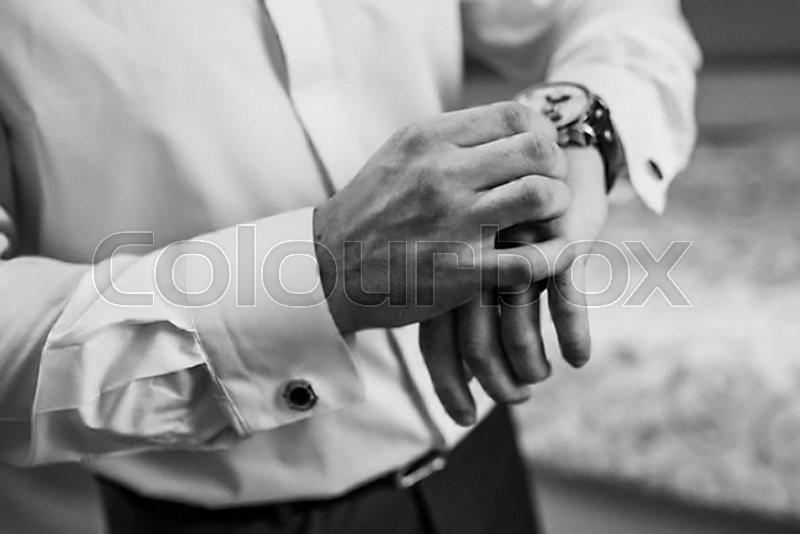 Stock image of 'Businessman checking the time on his wrist watch'