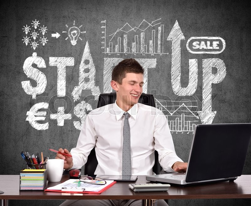 Stock image of 'businessman working in office and drawing start up scheme on wall'