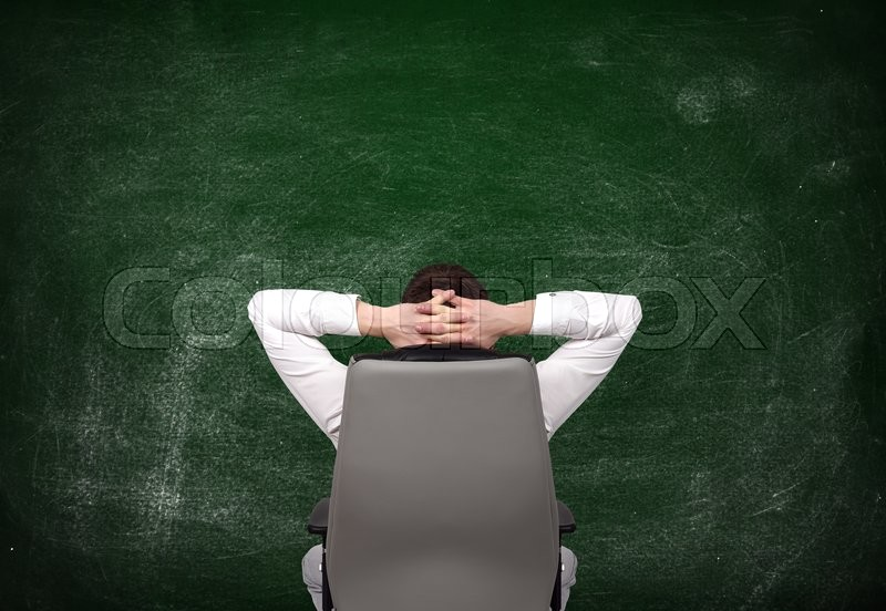 Stock image of 'relaxing businessman looking at blank chalk board'