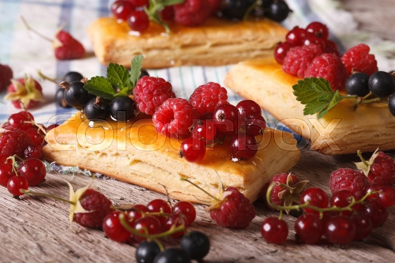 Homemade cakes with raspberries, currants, honey and mint on a table close-up. , stock photo