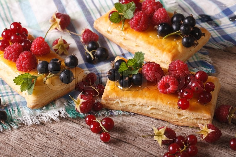 Stock image of 'Homemade small berry pies with honey and mint on a table close-up. horizontal\'