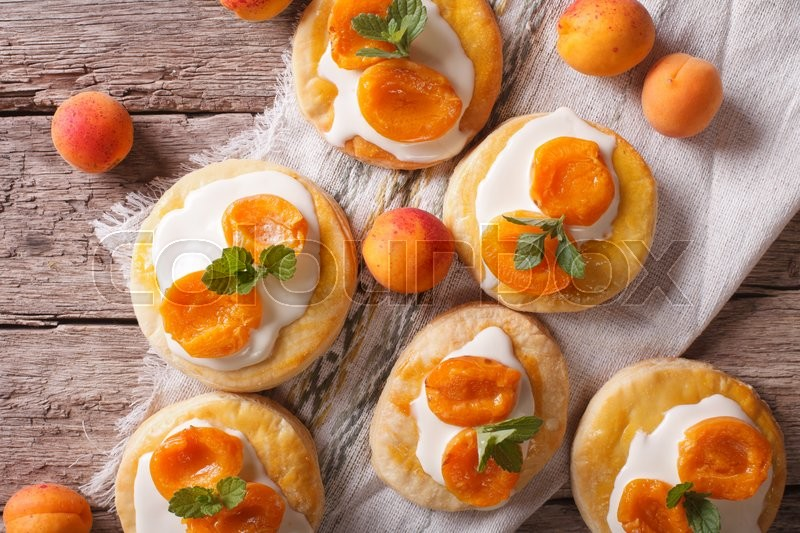 Stock image of 'Homemade apricot biscuits with white cream and mint on a table closeup. Horizontal top view\'