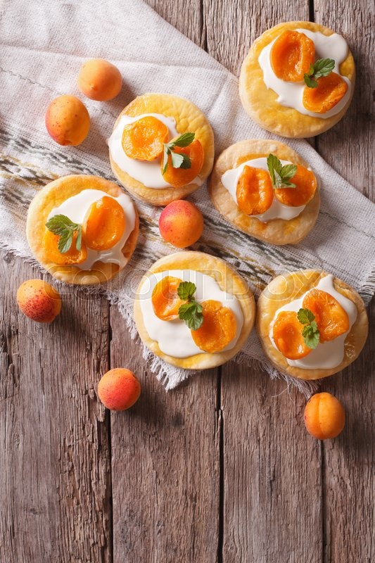 Stock image of 'Homemade apricot biscuits white cream and mint on a table. vertical top view\'