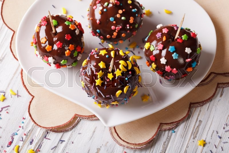 Stock image of 'Fresh apples in chocolate with candy sprinkles on a white plate. horizontal view from above\'