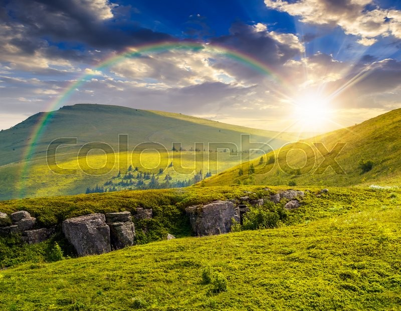 Stock image of 'view on high mountain peak from hillside covered with white boulders and conifer trees among green grass under the rainbow in evening warm light'