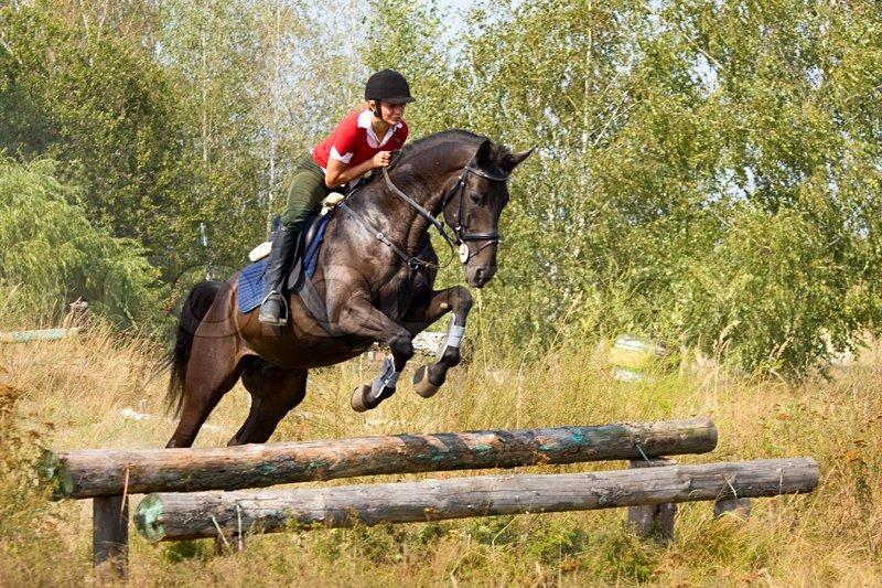 mädchen reiten auf einem pferd und sprung über hürde
