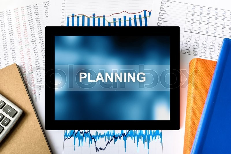 Stock image of 'planning word on tablet with financial graph background'