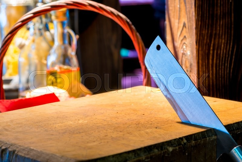 Stock image of 'Sharp knife jumper is placed in a wooden cutting board'