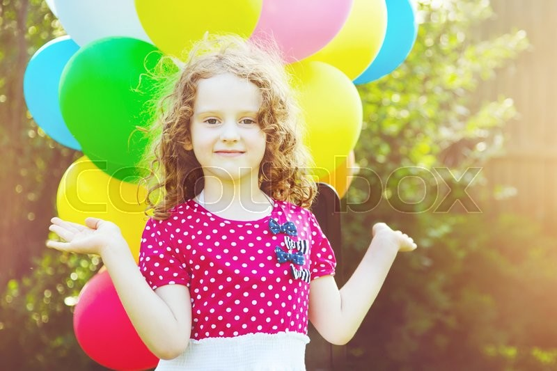 Stock image of 'Happy curly girl with colorful balloon in summer park. Toning to instagram filter.'