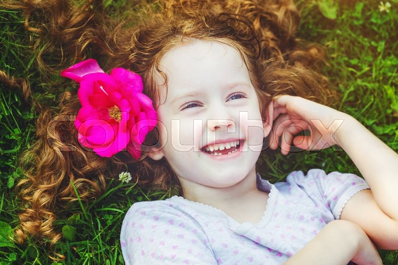 Stock image of 'Happy laughing girl with rose in her hair in green grass at summer park. Happy childhood concept.'