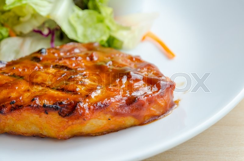 Stock image of 'Chicken steak on white dish with salad and bread'