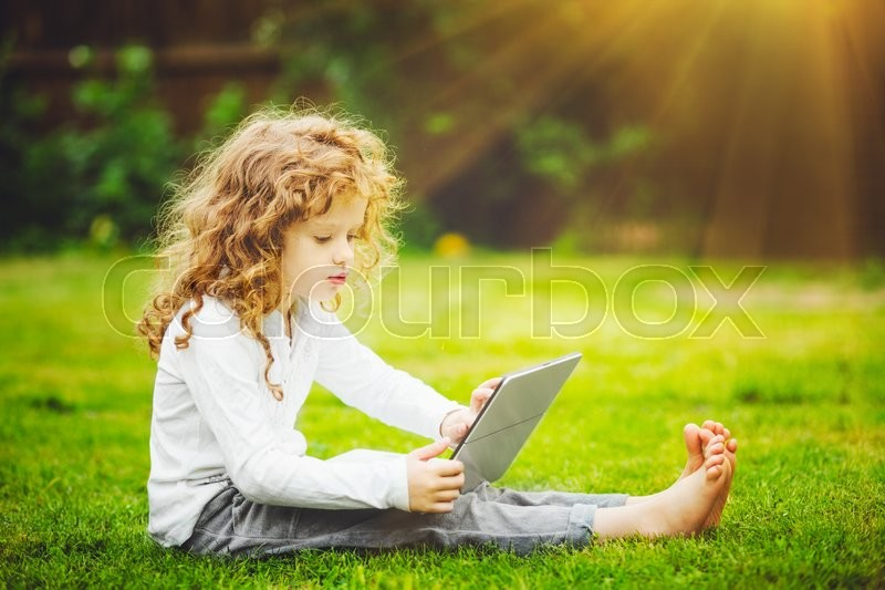 Stock image of 'Happy surprised child with laptop sitting on the grass.'