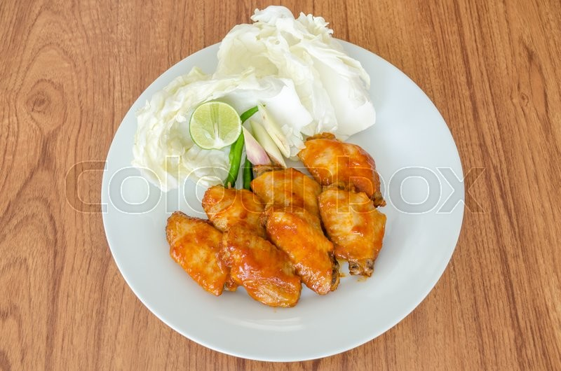Stock image of 'BBQ Chicken Wings on white dish'