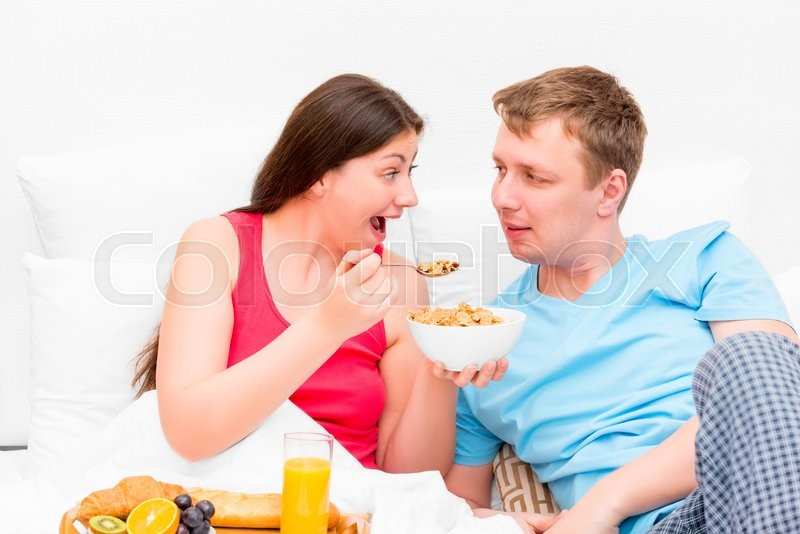 Stock image of 'Wife feeding her husband breakfast in bed'